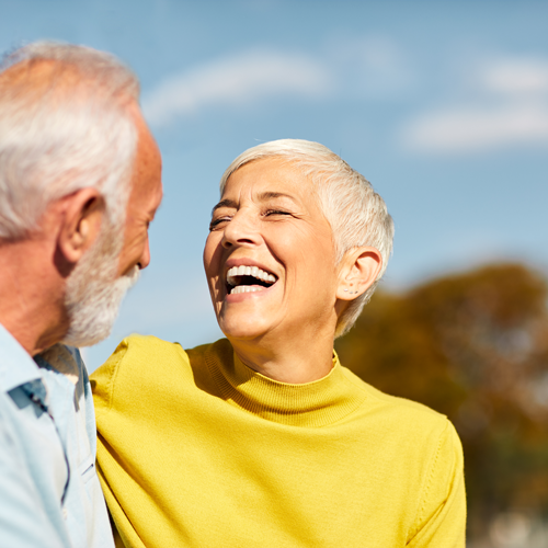 Laughing, happy couple with lady wearing dentures