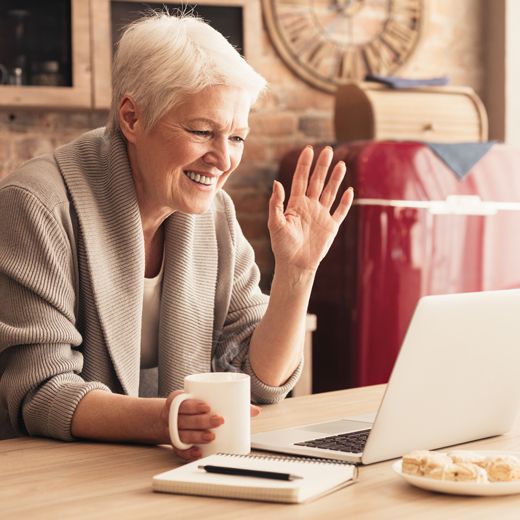 smiling lady wearing dentures waving on video call