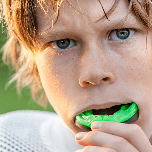 Young boy wearing a custom sports mouthguard